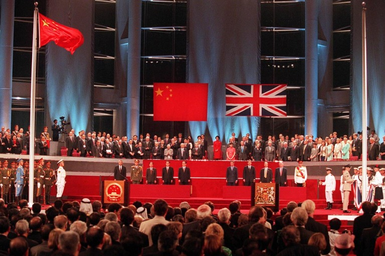 A general view of the handover ceremony showing the Chinese flag (L) flying after the Union flag (R) was lowered July 1, 1997. Hong Kong returned to Chinese sovereignty at midnight after 156 years of British colonial rule.  REUTERS/Kimimasa Mayama HONGKONG - RTR4ZIL